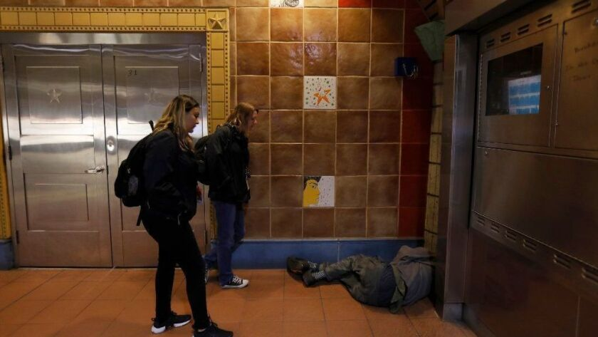 Jennie Mauries, left, and Karen Barnes of the social services agency People Assisting the Homeless, talk with a man sleeping at the Hollywood/Vine subway station last January.