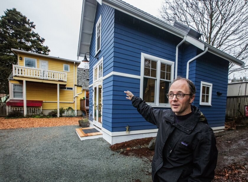 A Seattle homeowner points to a new backyard cottage he plans to rent out.