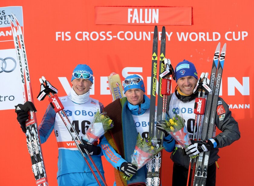 Winner Russia's Maksim Vylegzjanin, center, celebrates on the podium with second placed compatriot Aleksandr Bessmertnych, left, and third placed France Maurice Manificat after the men's 10km competition at the FIS Cross-Country World Cup in Falun, Sweden, Saturday Feb. 13, 2016. (Maja Suslin/TT vi