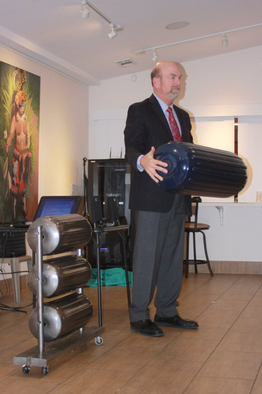 Town Council president Steve Haskins holds an actual-size plastic cylinder, standing next to a model of what the barrier could look like.