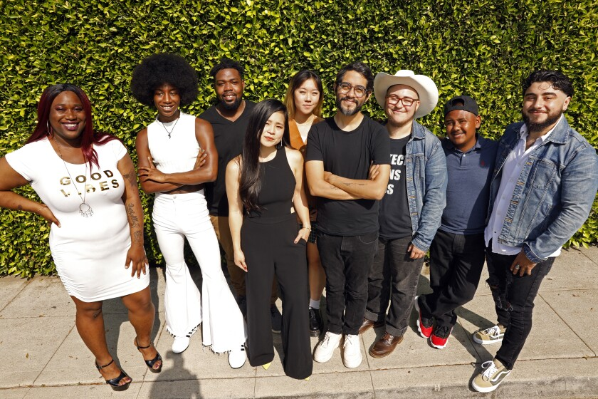 A diverse group of young adults stands on a sidewalk smiling at the camera.