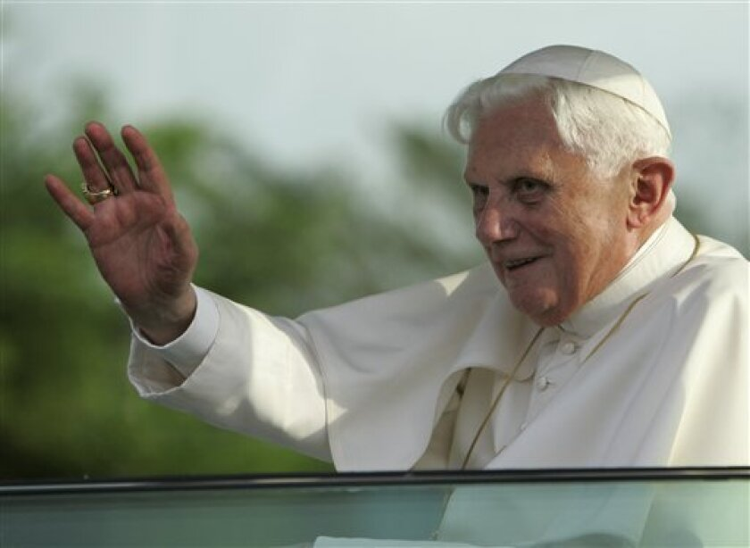 Pope Benedict XVI waves to a cheering crowd as he leaves the airport in Yaounde, Cameroon Tuesday, March 17, 2009. Pope Benedict arrived in Cameroon Tuesday on his first trip to Africa, the fastest-growing region for the Roman Catholic church. (AP Photo/Rebecca Blackwell)