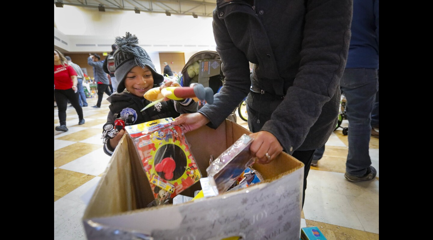 Three year-old Jeremy Norville, left, is all smiles as he and his mom, Ana Norville, right, look for stocking stuffers during the 28th annual Operation Holiday Joy event in the Murphy Canyon Chapel at The Armed Services YMCA San Diego. About 2,700 children of service members received holiday gifts during the event.