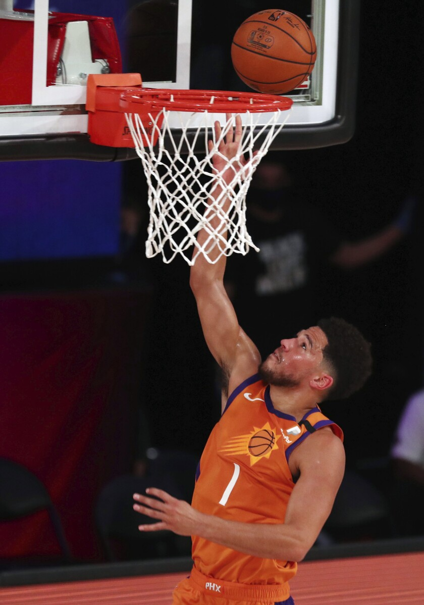 Devin Booker anota 27 puntos, Deandre Ayton agrega 24 unidades y 12 rebotes para que los Suns de Phoenix vencieran por 125-112 a los Wizards de Washington en su primer juego tras el reinicio de la liga el viernes 31 de julio del 2020. (Kim Klement/Pool Photo via AP)