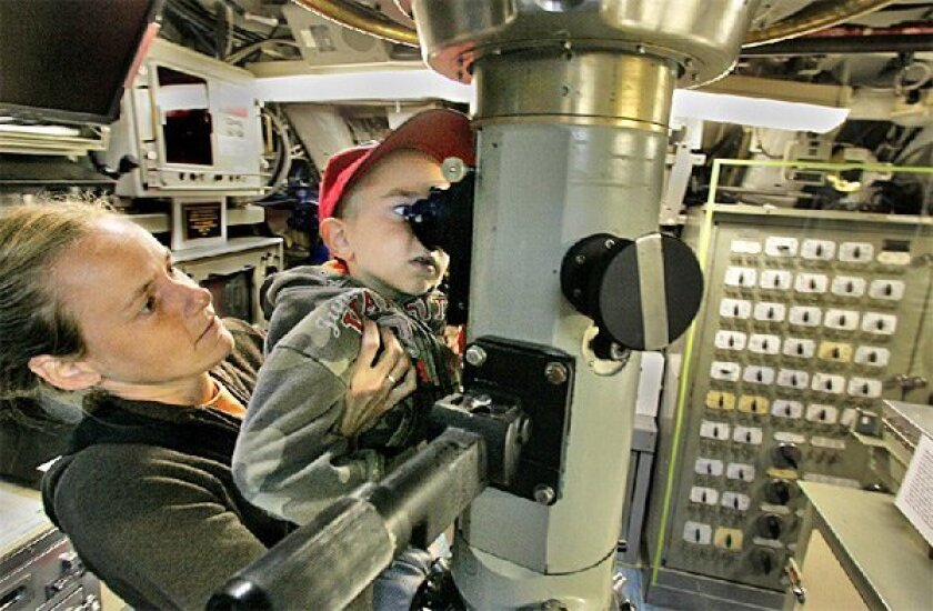 Japheth Nevin, 4, got a boost from his mother, Mandy, to look into the periscope aboard the research submarine Dolphin yesterday at the Maritime Museum of San Diego. (Eduardo Contreras / Union-Tribune)