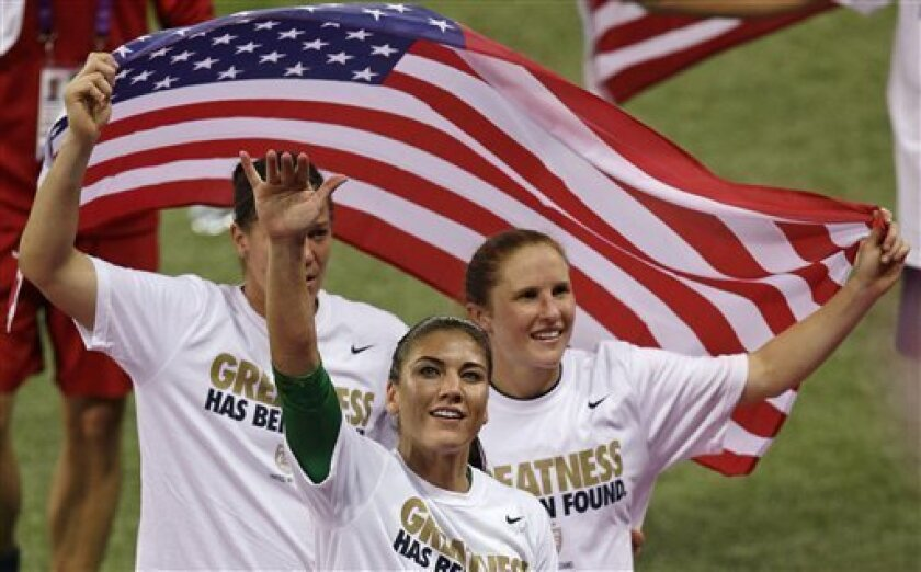 United States goalkeeper Hope Solo celebrates with teammates after winning the gold medal match against Japan at the 2012 Summer Olympics, Thursday, Aug. 9, 2012, in London. The U.S. women's football team won its third straight Olympic gold medal Thursday, beating Japan 2-1 in a rematch of last year's World Cup final and avenging the most painful loss in its history. (AP Photo/Andrew Medichini)