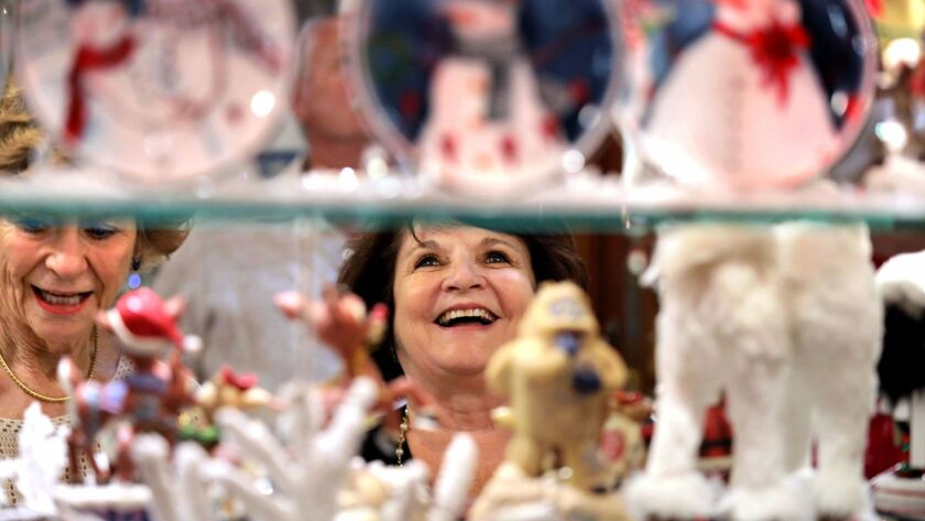 Judy Willoughby, left, and friend Barbara Altbaum, at right, get a close look at the shelves full of