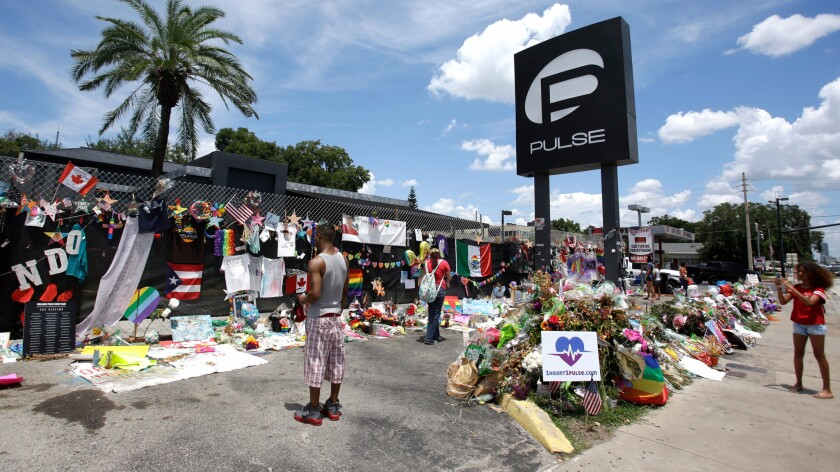 Visitors leave items at a makeshift memorial outside the Pulse nightclub in Orlando, Fla. on July 11, 2016.