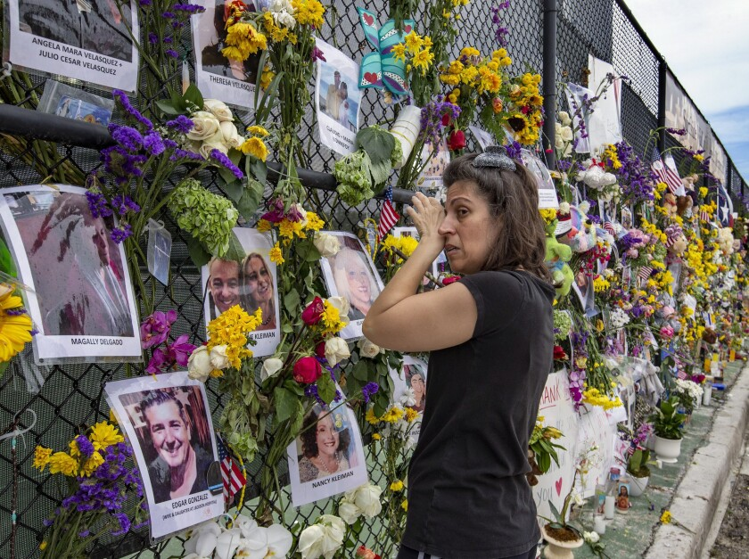 Gini Gonte visits the Surfside Wall of Hope & Memorial on Wednesday, July 7, 2021, as she honors her friends Nancy Kress Levin and Jay Kleiman, who lost their lives after the collapse of the Champlain Towers South in Surfside, Fla. (Al Diaz/Miami Herald via AP)