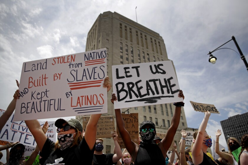 People hold signs during a June 5 rally in downtown Kansas City, Mo., to protest the death of George Floyd