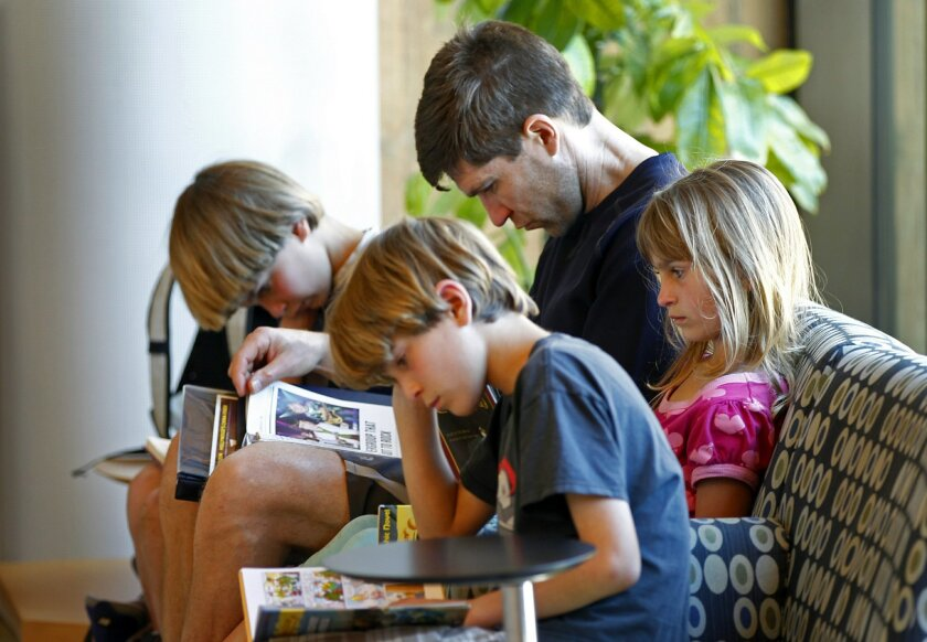 David Manternach reads with his children, Kyle, 8, left, Una, 6, right, and Aidan, 9, front, at the Encinitas Library on Saturday.