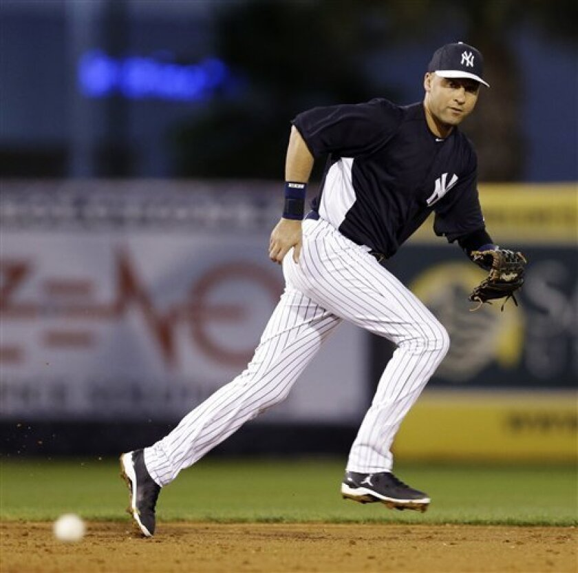 New York Yankees shortstop Derek Jeter chases down an RBI single by Philadelphia Phillies' Domonic Brown during the third inning of their exhibition spring training baseball game in Tampa, Fla., Wednesday, March 13, 2013. The game marked Jeter's first time playing the field since breaking his left