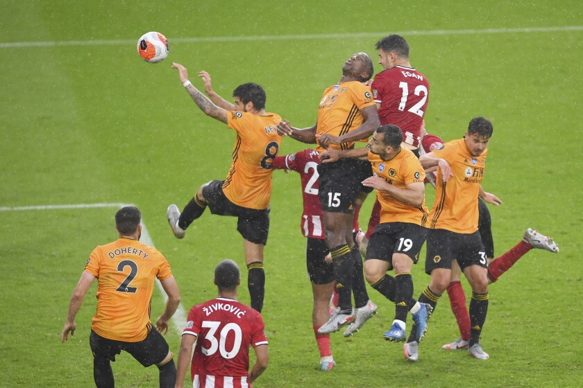 Sheffield United's John Egan heads the ball to score a goal during the English Premier League soccer match between Sheffield United and Wolverhampton Wanderers at Bramall Lane stadium in Sheffield, England, Wednesday, July 8, 2020. (Laurence Griffiths/Pool via AP)
