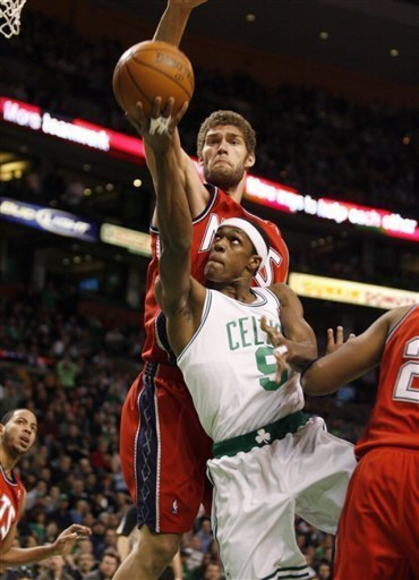 Boston Celtics' Rajon Rondo (9) drives to the basket ahead of New Jersey Nets' Brook Lopez, back, during the first half of an NBA basketball game in Boston, Friday, Feb. 5, 2010. (AP Photo/Mary Schwalm)