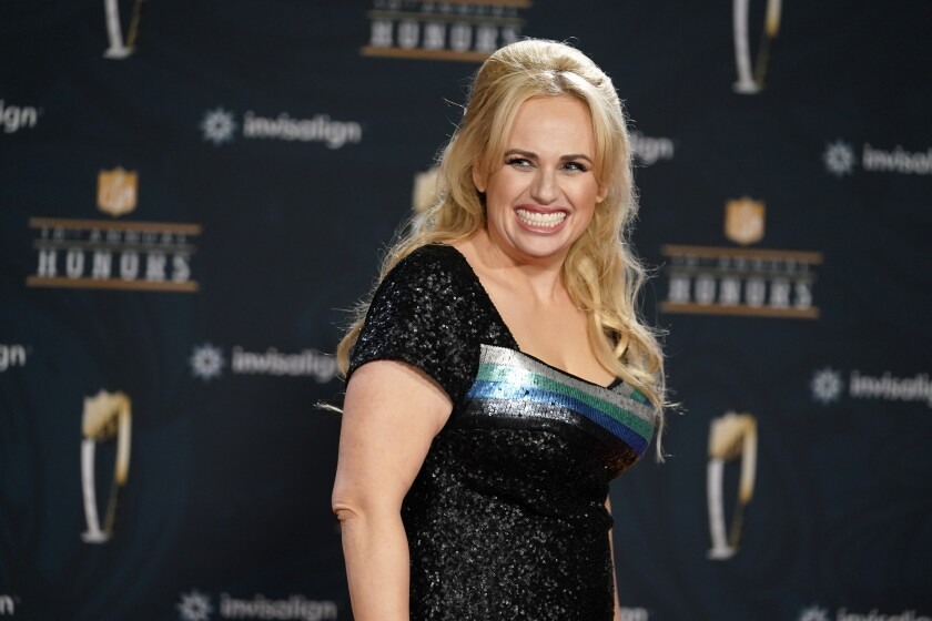 """FILE - In this Tuesday, Feb. 2, 2021, file photo, Rebel Wilson poses on the red carpet during the NFL Honors football awards show, in Los Angeles. Wilson returns to her roots as host of ABC's """"Pooch Perfect,"""" an eight-episode series featuring 10 dog groomers and their assistants competing in challenges. The show, which debuts March 30, is based on an Australian version. (AP Photo/Marcio Jose Sanchez, File)"""