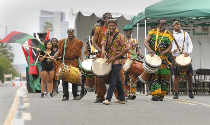Members of an African drum and dance company lead a Juneteenth parade in 2018.