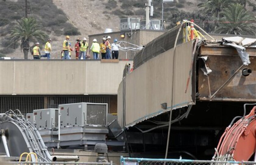 Border officials and emergency personnel look over the construction site where a scaffolding collapsed at the San Ysidro Port of Entry in San Diego Wednesday, Sept. 14, 2011. Three people have been taken to hospitals after construction scaffolding collapsed on cars at the nation's busiest border crossing connecting San Diego and Tijuana, Mexico. (AP Photo/Denis Poroy)