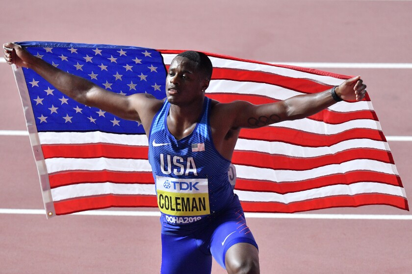 Christian Coleman poses with a U.S. flag after winning the 100-meter race at the 2019 world championships in Doha, Qatar.