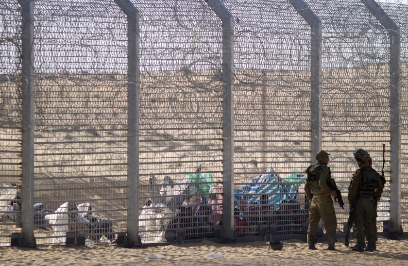 African refugees sit behind a border fence after attempting to cross from Egypt into Israel as Israeli soldiers stand guard nearby.