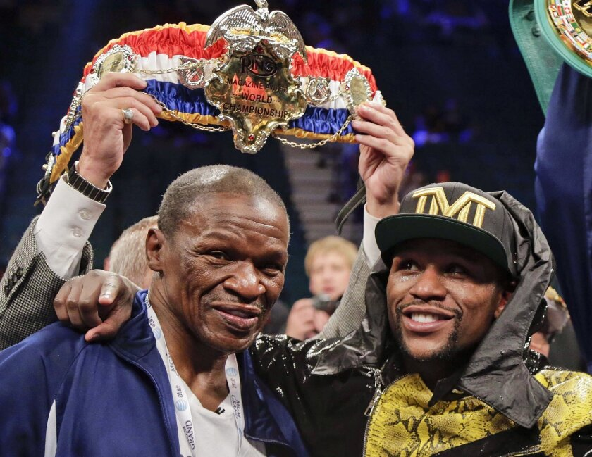FILE - In this May 4, 2013, file photo, Floyd Mayweather Jr., right, poses for photos with his father, Floyd Mayeather Sr. after defeating Robert Guerrero by unanimous decision in a WBC welterweight title fight in Las Vegas. He taught his son to throw punches before he could walk, and he'll be in his corner for the biggest fight of his life against Manny Pacquiao on May 2. The relationship betwee Mayweather Sr. and his son, though, hasn't always been good. (AP Photo/Rick Bowmer, File)
