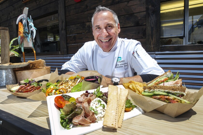 Barry Schneider, executive chef for the Del Mar Fairgrounds' Premiere Food Services, displays several dishes on the menu at the new Emerald Farms Eatery, in the garden area, at the San Diego County Fair, which opens its summer run on Friday, May 31.