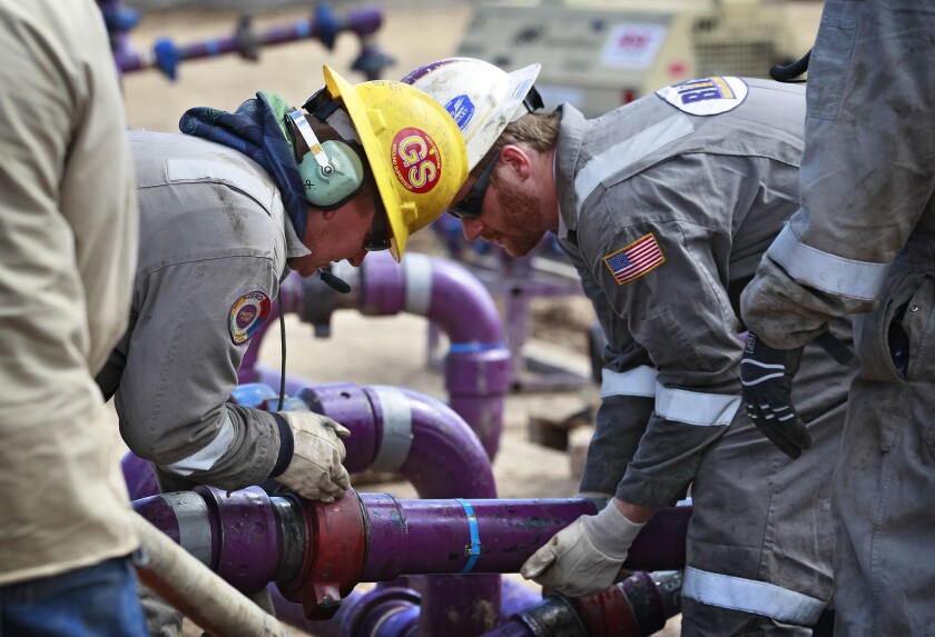 Workers adjust piping at an Encana Oil & Gas (USA) Inc. drilling site in western Colorado.