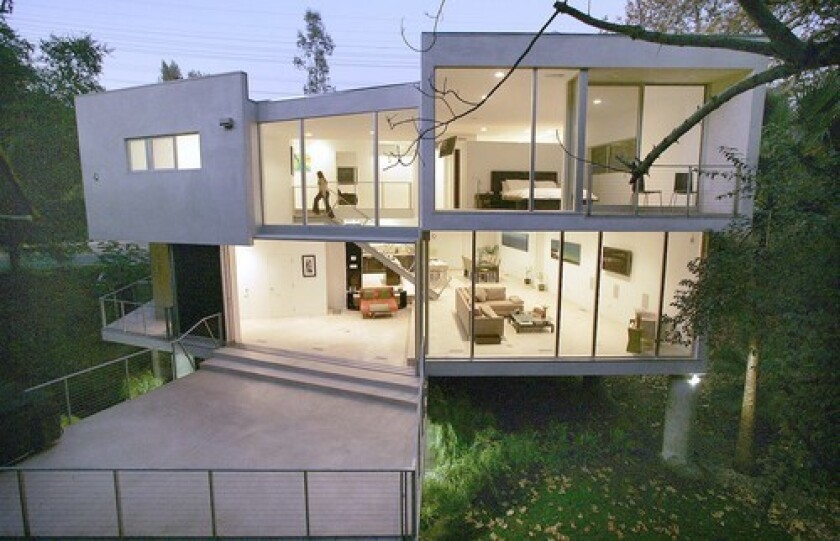 """When a family friend suggested to Corrine Glass that she buy the Studio City lot, her response was: """"You're absolutely out of your mind."""" The parcel had stood vacant for decades, declared unbuildable by previous would-be buyers. Its steep slope made construction impractical, and a creek ran though the feral landscape. But three years and more than a few panic attacks later, Glass has a house that is a realm of peace and quiet. From her minimalist, open-plan kitchen, dining area and living room, she can admire her former nemeses: the wooded hill and burbling creek, now defining features of the home. While city traffic rushes by the front of the house, wilderness beckons from behind."""