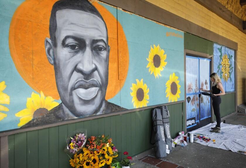 A woman paints a mural in La Mesa, California.