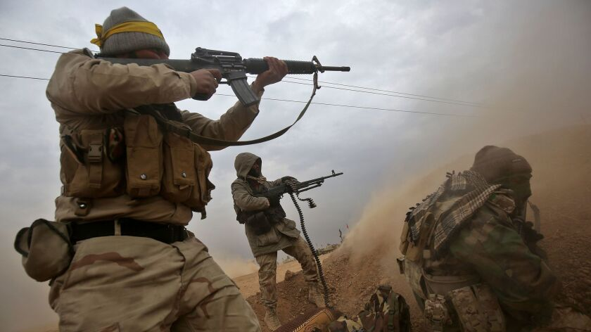 Iraqi Shiite fighters from a Popular Mobilization militia fire their weapons as they advance near the town of Tall Abtah, south of Tall Afar, on Nov. 30, 2016.