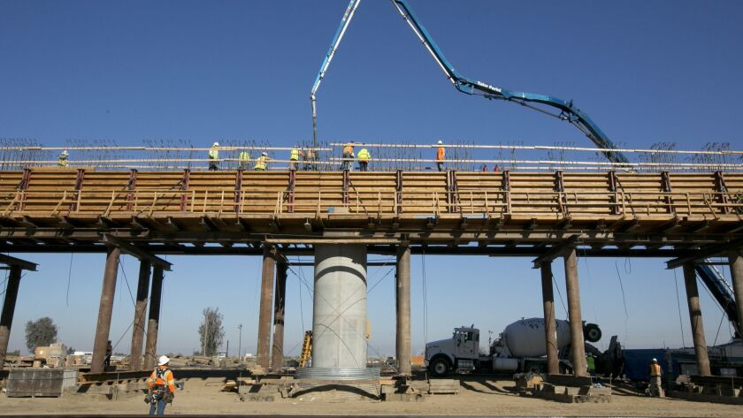 FILE - In this Dec. 6, 2017, file, workers pour concrete on to one of the elevated sections of the h
