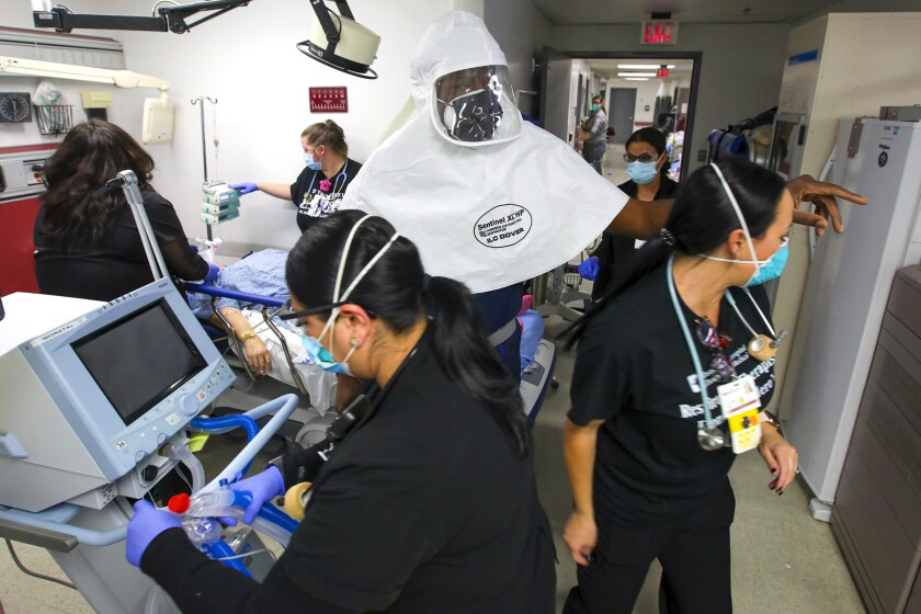 Healthcare workers in protective gear in a hospital around a patient's bed