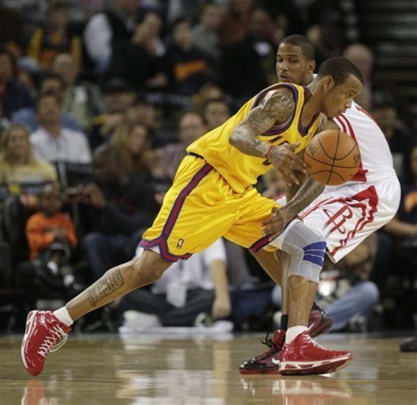 Golden State Warriors' Monta Ellis, left, dribbles around Houston Rockets' Trevor Ariza during the first half of an NBA basketball game in Oakland, Calif., Thursday, Dec. 3, 2009. (AP Photo/Marcio Jose Sanchez)