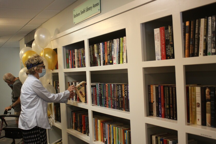 A Chateau La Jolla resident grabs a book from the new Barbara Smith Library Annex.