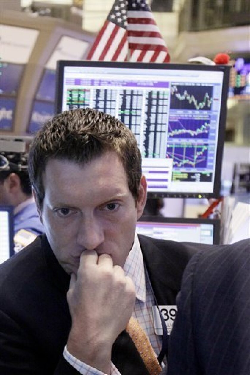 FILE - In this June 22, 2011 file photo, specialist William Bott looks at a screen as he works on the floor of the New York Stock Exchange. For investors, June was one long seesaw ride that began with a deep plunge on the first day of the month. Seven days of declines were followed by four days of