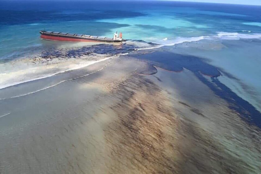 """This photo taken and provided by Georges de La Tremoille of Mu Press shows oil leaking from the MV Wakashio, a bulk carrier ship that recently ran aground off the southeast coast of Mauritius, Friday, Aug. 7, 2020. The Indian Ocean island of Mauritius declared a """"state of environmental emergency"""" late Friday after a Japanese-owned ship that ran aground offshore days ago began spilling tons of fuel. (Georges de La Tremoille/MU press via AP)"""