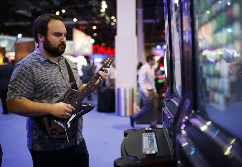 """FILE - In this Sept. 30, 2015, file photo, Brett Boge of Reno, Nev., plays Guitar Warrior by G2 Game Design during the Global Gaming Expo in Las Vegas. Massachusetts Gaming Commission members met on Thursday, Feb. 18, 2016, to discuss draft regulations for so-called """"skill-based"""" slot machines that"""