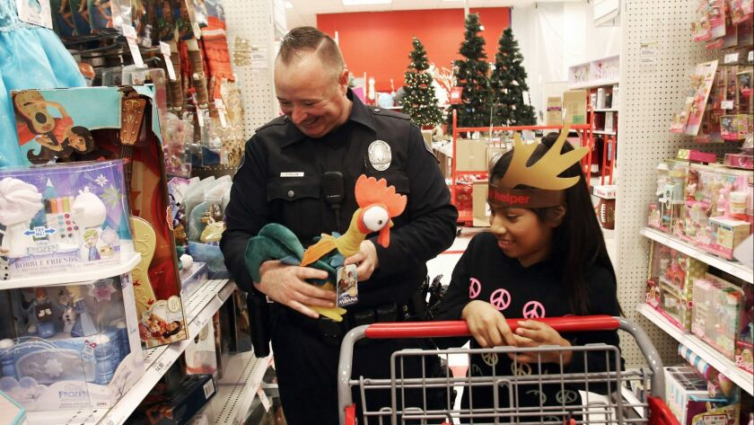 Glendale Police Officer James Colvin, and Alice Aguilar, 11, are all smiles as they shop for toys du