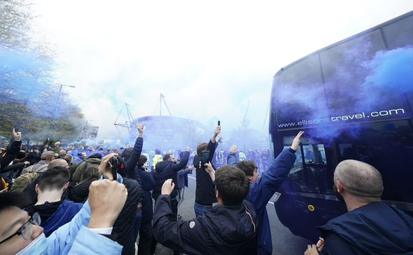 Manchester City supporters greet the team coach as they gather outside the Etihad stadium in Manchester, England, Saturday, May 8, 2021 where the England Premier League match between Manchester City and Chelsea is to be played. City fans are hoping that a win on Saturday will see their team clinch the English Premier League title. (AP Photo/Jon Super)