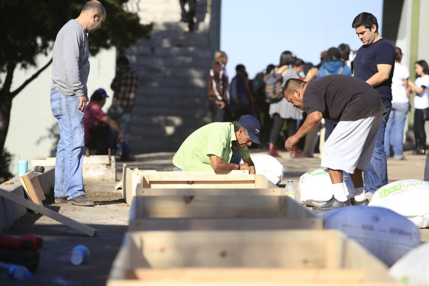 Bordofarms volunteers build boxes by the Tijuana River for an urban farming project aimed at helping U.S. deportees.