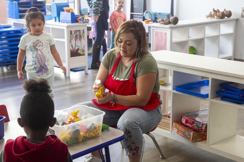 Consuelo Garcia sanitizes toys at the Children of the Rainbow child-care center in San Diego.