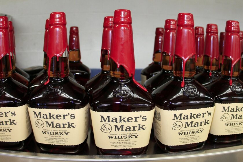 Bottles of Maker's Mark Distillery Inc. bourbon whisky sit on a conveyor belt after being hand dipped with their signature red wax at their distillery in Loretto, Kentucky, U.S., on Tuesday, Jan. 4, 2011.