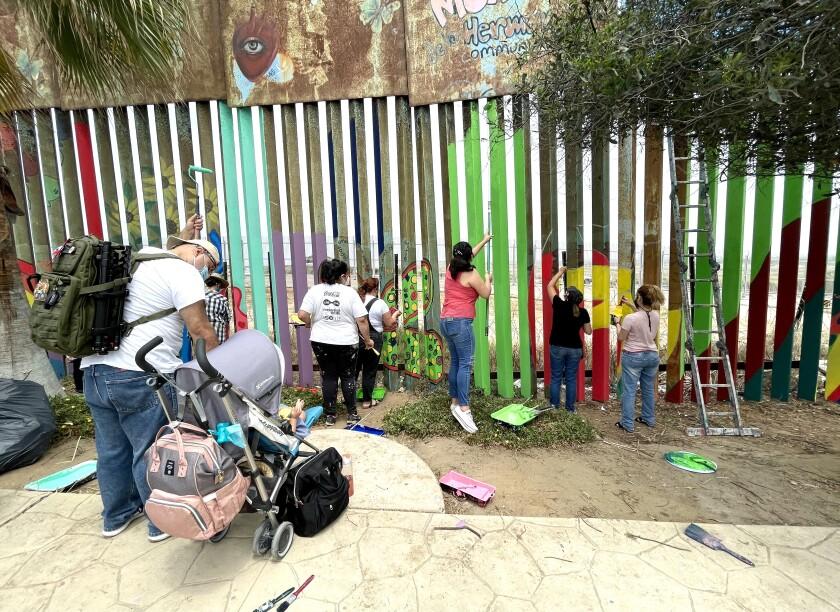 Voluntarios pintan tramo del muro fronterizo en Playas de Tijuana este sábado 24 de julio de 2021.