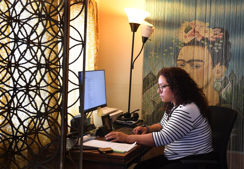 Jackie Cornejo sits in her home office in Los Angeles, where she makes vaccination appointments for her extended family.