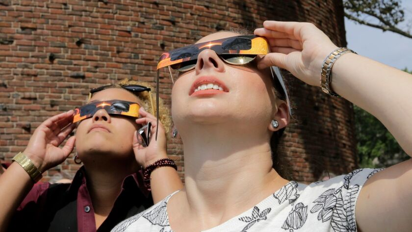 Liz Jason, of Boston, right, uses protective eclipse glasses to view a partial solar eclipse, Monday