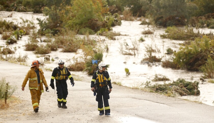 Los Angeles fire special op and swift water team members walk along the L.A. River at the Fletcher Drive bridge after rescuing someone from high water Tuesday morning.