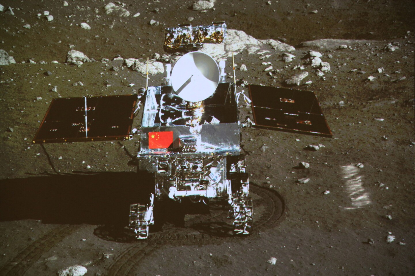 This image taken by the on-board camera of the lunar lander Chang'e 3 shows China's first moon rover, Yutu, on the lunar surface in the area known as the Bay of Rainbows. The rover left deep tracks in the loose lunar soil, state media reported Sunday.
