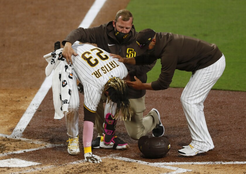 Padres' Fernando Tatis Jr. is helped at home plate Monday by assistant athletic trainer Ben Fraser and manager Jayce Tingler.