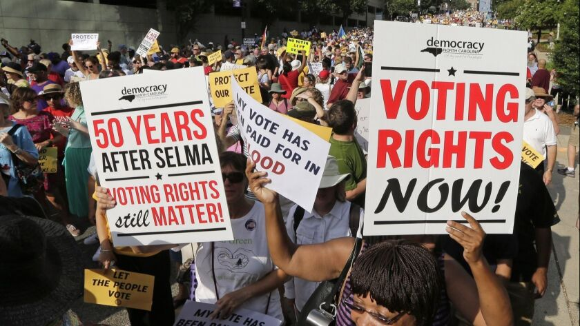 Demonstrators march through the streets of Winston-Salem, N.C., on July 13, 2015, after the beginning of a federal voting rights trial challenging a 2013 state law.