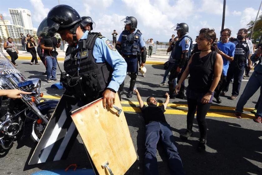 La policía trata de evitar que un grupo de manifestantes en San Juan, Puerto Rico. EFE/Archivo