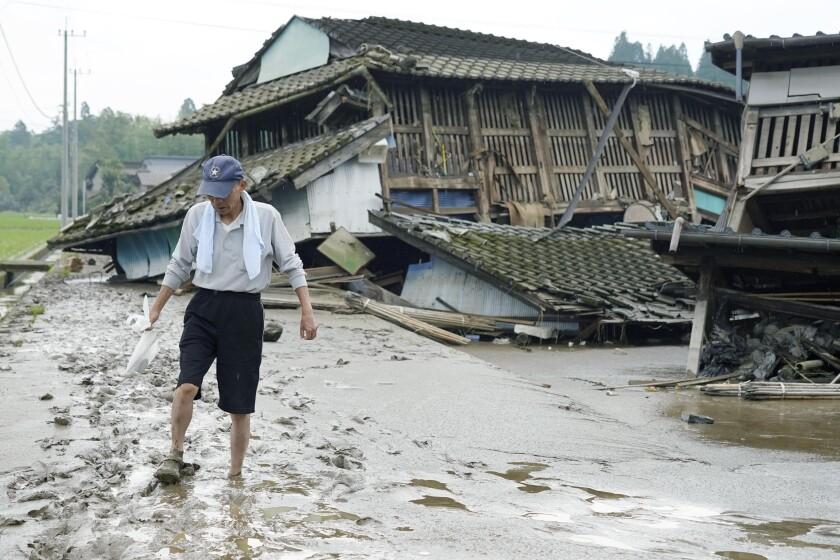 A man walks on muddy road past houses damaged by flood in Kuma village, Kumamoto prefecture, southwestern Japan.